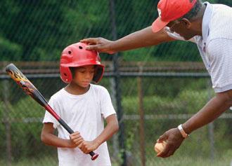 「こうやって公園の外までボールをかっ飛ばすんだ」。高齢の元野球選手が、伸び盛りの少年選手に教える。米国ではスポーツのコーチングに多くのボランティアが集まる(©AP Images/Richmond Times-Dispatch, Alexa Welch Edlund)