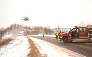 幹線道路で発生した交通事故の負傷者を病院に搬送するため、雪の積もった野原にヘリコプターを誘導着陸させるラファージ消防隊の隊員 (courtesy of Philip Stittleburg)