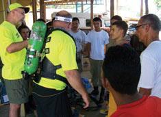 ロアタン島(ホンジュラス)の消防士に、炎上中の建物に入る際の呼吸エアーパックの装着手順を指導するロン・グルーニング(左)(Rick Markley/IFRM)