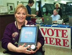 テキサス州オースチンで、新しい投票の注意書きを見せる選挙事務員 (©Harry Cabluck/AP Images)