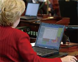 州議会は、州レベルでは州知事室に匹敵する権限を持つ。写真は2003年、テキサス州上院議場でノートパソコンを使って資料を調べる同州上院議員