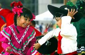 メキシコのダンスを踊る「ソチクェツァル・ティクン」(アラスカの子供たちのグループ)のアーリート・デル・リアル(左、5歳)とハビエル・アクーナ(6歳)。アラスカ州アンカレッジで開かれた「ミート・ザ・ワールド」のイベントで。(AP/WWP)