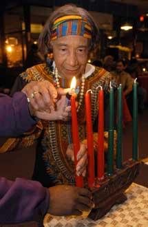アフリカ系米国人の祝日である「クワンザ」初日の夜、ろうそくに火をつける ティナ・ソロモン(88)。マサチューセッツ州ブロックトンにて(AP/WWP)