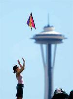 シアトルのスペースニードルのそばで、凧を飛ばす人 (© AP Images/Elaine Thompson)