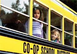 スクールバスから物珍しそうに外をながめる子供たち。米国の地方政府には、さまざまな形態があるが、中でも学校区には、しばしば人々の最も高い関心が集まる。学校区は大きな自治権を持っており、教育政策を定めている