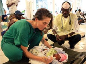 2010年ハイチ地震で、負傷者の治療に一緒に取り組むPIHの米国人とハイチ人のボランティア(©Partners In Health)
