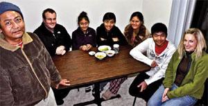 ビルマから到着したばかりのリアナ一家を訪れて雑談を交わし、シアトルでの生活に慣れるのを手助けするジャレッド・マイヤーズ(左から2人目)とレイナ・スウィフト(右)(photograph by Jonathan Dodds)