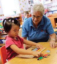 遠い国から来た見知らぬ人びとと知識を共有したいという思いが、米国の多くのボランティアに活気を与えている。高齢のボランティアの中には、児童の学習指導や助言役を引き受けている人も多い(©St. Petersburg Timnes/Gail Diederich/The Image Works)